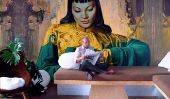 Wayne Hemmingway read a newspaper in his apartment - Tretchikoff painting (repro) takes up the whole wall.